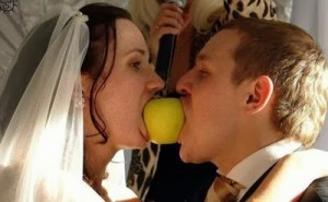 Bride and groom with an apple in their mouth